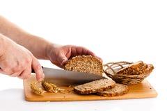 Obsługuje ręka tnącego chleb odizolowywającego na białego tła zdrowym jedzeniu Obrazy Royalty Free