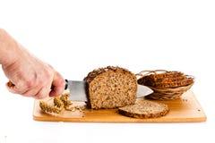 Obsługuje ręka tnącego chleb odizolowywającego na białego tła zdrowym jedzeniu Obrazy Stock