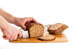 Obsługuje ręka tnącego chleb odizolowywającego na białym tle Fotografia Stock