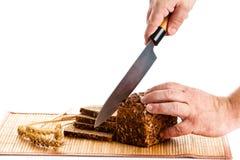 Obsługuje ręka tnącego chleb odizolowywającego na białym tle Zdjęcia Stock