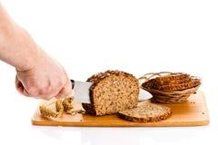 Obsługuje ręka tnącego chleb odizolowywającego na białym tle Zdjęcia Royalty Free