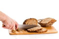 Obsługuje ręka tnącego chleb odizolowywającego na białym tle Obrazy Stock