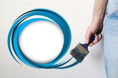 Obsługuje ręki mienia paintbrush farby błękitny kolor rysującego okrąg na białej kolor ścianie, bezpłatna przestrzeń dla twój tek fotografia stock