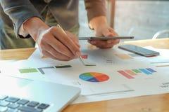 Obsługuje ręki mienia pióro wskazuje wykres na biurku, inni ręk uses a Zdjęcie Royalty Free
