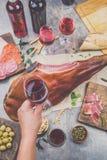Obsługuje ręki mienia wina szkła frome above stół z zakąskami, całą nogą baleronu serrano i czerwienią spanit lub włocha, Obrazy Royalty Free