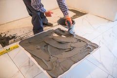 Obsługuje ręki troweling adhezyjny dla ceramicznej płytki podłoga ceramiczne target1908_0_ płytki obraz stock