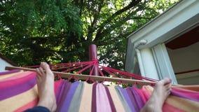 Obsługuje relaksować na kolorowym hamaku w letnim dniu Młodego faceta łgarski puszek bierze drzemkę Krzyżować nogi w długich błęk zbiory