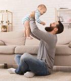 Obsługuje rzucać w górę jego syna w żywym pokoju w domu zdjęcie royalty free