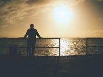 Obsługuje samotnego pobyt na morze moście i ogląda zadziwiającego wschód słońca zdjęcie royalty free