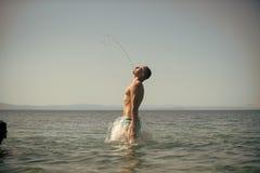 Obsługuje skok z morza z pluśnięciami woda piękni pojęcia basenu wakacje kobiety potomstwa Facet w swimwear robi strumieniowi wod obrazy royalty free