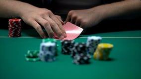 Obsługuje sprawdza karty i dźwiganie, bluffujący podczas grzebaka turnieju, szansa wygrywać fotografia stock