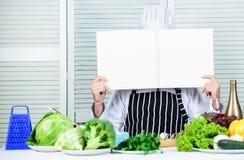Obsługuje szefa kuchni w kapeluszu i fartuch czytającej książce E r Pożytecznie książka dla gotować zdjęcia royalty free