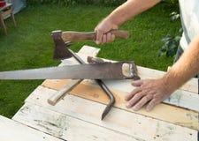 Obsługuje trzymać cioskę, pracuje z budów narzędziami w jego ogródzie Obrazy Stock