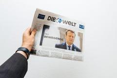 Obsługuje trzymać Die Welt gazetowy z Emmanuel Macron na pierwszy pag Obrazy Stock