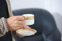 Obsługuje trzymać filiżankę herbata lub kawa w ręce obrazy royalty free