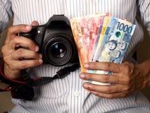 Obsługuje trzymać Filipińskiego peso rachunki i kamerę zdjęcie stock