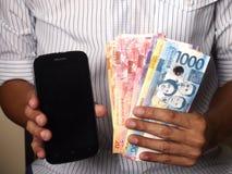 Obsługuje trzymać Filipińskiego peso rachunki i smartphone obrazy royalty free
