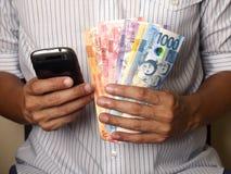 Obsługuje trzymać Filipińskiego peso rachunki i smartphone obrazy stock