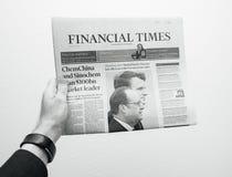 Obsługuje trzymać Financial Times gazetowy z Emmanuel Macron na fi Zdjęcia Stock