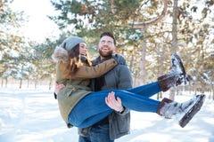 Obsługuje trzymać jego dziewczyny na rękach w zima parku Zdjęcia Royalty Free