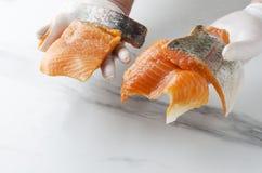 Obsługuje trzymać kilka kawałki świeży surowy łosoś Smakowici kawałki ryba obrazy royalty free