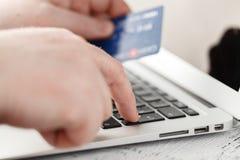 Obsługuje trzymać kredytową kartę w ręce i wchodzić do ochrona kod używać laptop klawiaturę Fotografia Royalty Free