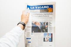 Obsługuje trzymać Le Figaro gazetowy z Emmanuel Macron na pierwszy pa Zdjęcie Stock