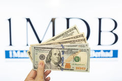 Obsługuje trzymać Malezja Ringgit z burr 1MDB tłem wskazuje USA rzędu Obrazy Royalty Free