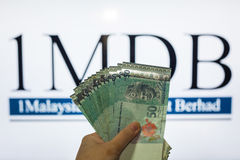 Obsługuje trzymać Malezja Ringgit z burr 1MDB tłem wskazuje USA rzędu Obraz Royalty Free