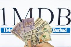 Obsługuje trzymać Malezja Ringgit z burr 1MDB tłem wskazuje USA rzędu Zdjęcie Stock