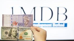 Obsługuje trzymać Malezja Ringgit z burr 1MDB tłem wskazuje USA rzędu Obraz Stock