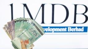 Obsługuje trzymać Malezja Ringgit z burr 1MDB tłem wskazuje USA rzędu inves Zdjęcia Stock