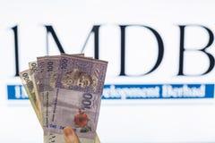 Obsługuje trzymać Malezja Ringgit z burr 1MDB tłem wskazuje USA rzędu inves Zdjęcie Royalty Free