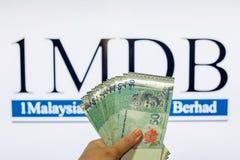 Obsługuje trzymać Malezja Ringgit z burr 1MDB tłem wskazuje USA rzędu inves Obraz Royalty Free