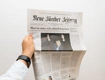 Obsługuje trzymać Neue Burcher Zeitung gazetowy z Emmanuel Macron Fotografia Stock