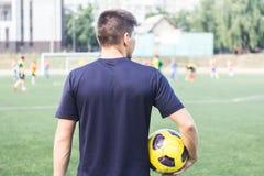 Obsługuje trzymać piłki nożnej piłkę na polu Fotografia Royalty Free