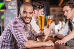 Obsługuje trzymać szkło piwo w ręce podczas gdy siedzący przy barem Th Zdjęcie Royalty Free