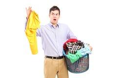 Obsługuje trzymać zaśmierdłą bluzkę i pralnianego kosz Zdjęcie Stock