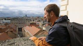 Obsługuje turysty cieszy się breathtaking pejzaż miejskiego, męski patrzeć na miasto dachach zbiory
