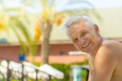 Obsługuje uśmiecha się kamera, relaksuje pływackim basenem w kurorcie fotografia royalty free