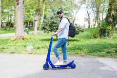 Obsługuje używać błękitną elektryczną hulajnoga w parku zdjęcia royalty free