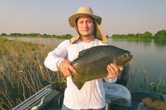 Obsługuje używać kapeluszową i białą koszula trzyma ryba na pokładzie łodzi fotografia stock