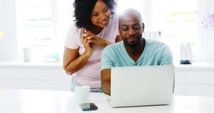 Obsługuje używać laptop podczas gdy kobieta opowiada na telefonie komórkowym 4k zbiory wideo