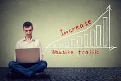 Obsługuje używać laptop pracuje na planie wzrastać strona internetowa ruch drogowego Technologii marketingowy pojęcie Zdjęcie Royalty Free