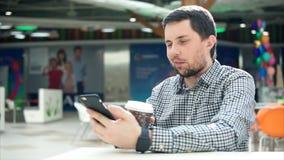 Obsługuje używać mądrze telefon i pijący kawę w centrum handlowym zbiory wideo