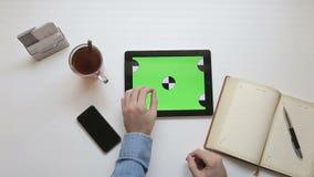 Obsługuje używać pastylkę z zielonym tłem w miejscu pracy zdjęcie wideo