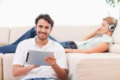 Obsługuje używać pastylka komputer podczas gdy jego żona słucha muzyka obraz royalty free
