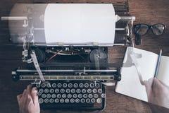 Obsługuje używać rocznika ręcznego maszyna do pisania na nieociosanym drewnianym stole z ruch plamy opłatą kareciany powrót Zdjęcia Stock