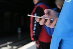 Obsługuje używać telefon komórkowego outdoors na ulicie zdjęcie royalty free