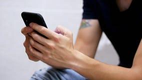 Obsługuje używa mądrze telefon w toalecie, surfuje internet W górę męskich ręk trzyma telefon zbiory